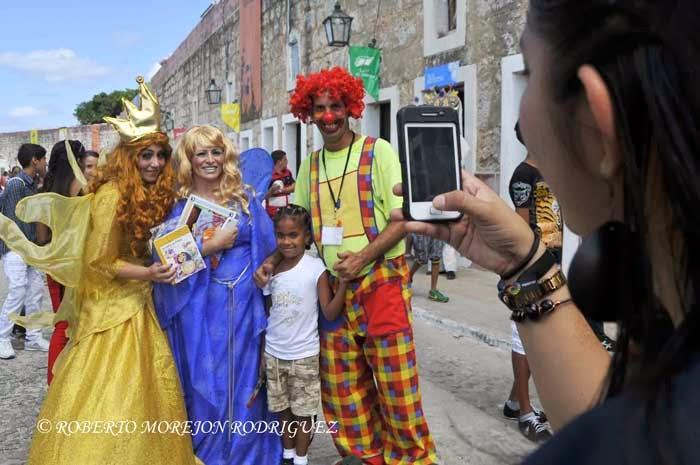 Una niña se toma una foto con hadas y payaso en el Pabellón de Ecuador, durante su visita a la XXIII Feria Internacional del Libro Cuba 2014, en su sede principal, la Fortaleza San Carlos de la Cabaña, en La Habana, el 16 de febrero de 2014.