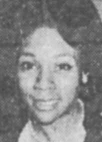 Black and white headshot of a Black woman in her 30s, with large almond-shaped eyes and neatly coiffed hair