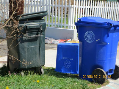 Trash can and recycling containers set on grass next to driveway.