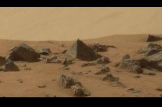 """Uma imagem capturada em Marte pelo robô Curiosity, da NASA, levantou inúmeras teorias de entusiastas sobre a vida fora da Terra. Em uma foto enviada pelo rover pode-se notar à primeira vista uma formação de uma pirâmide. Seria uma ilusão causada pela luz ou uma prova de civilização alienígena? De acordo com a imagem, a suposta pirâmide teria o tamanho de um pequeno carro. Apesar de muita gente defender que tudo não passa de um efeito de luzes e sombras, o canal do Youtube ParanormalCrucible vai mais longe e insiste que a formação """"é próxima de um formato e desenho perfeitos"""" e que a pirâmide é o """"resultado de obra de vida inteligente e certamente não se trata de uma ilusão de luz e sombras"""", além de informar que pirâmides também podem servir de """"guias para viajantes""""."""