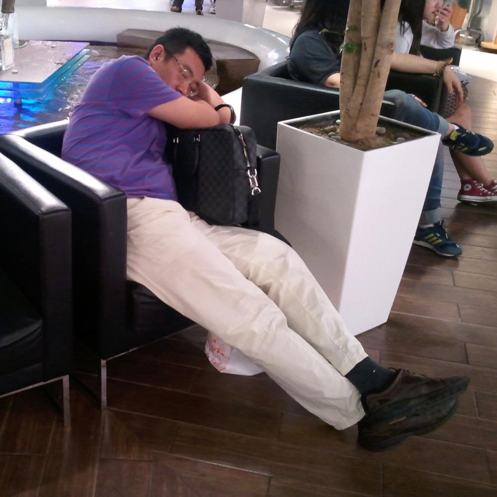 Hombre coreano durmiendo en un centro comercial
