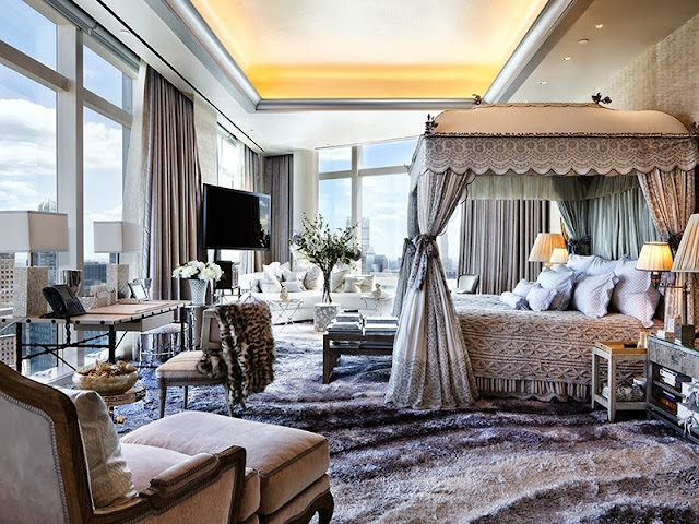 Master bedroom with wrap around floor to ceiling windows, plush rugs and a large canopy bed