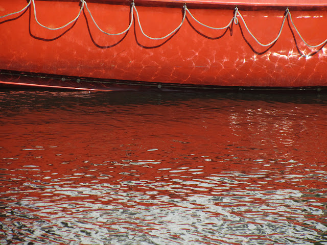 orange dinghy and its reflection