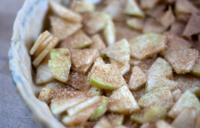 Manzanas troceadas con azúcar y canela en la tarta de mazana