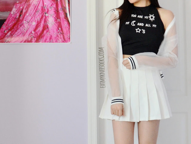A monochromatic grunge-rock outfit featuring Dresslink's sheer striped bomber jacket and halter crop top, worn with a white pleated American Apparel tennis skirt.