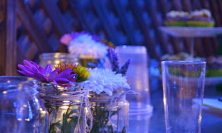 Tabletop with jars containing either tea light candles or flowers. A two-tiered cake stand with cupcakes is in the background on the right hand side.