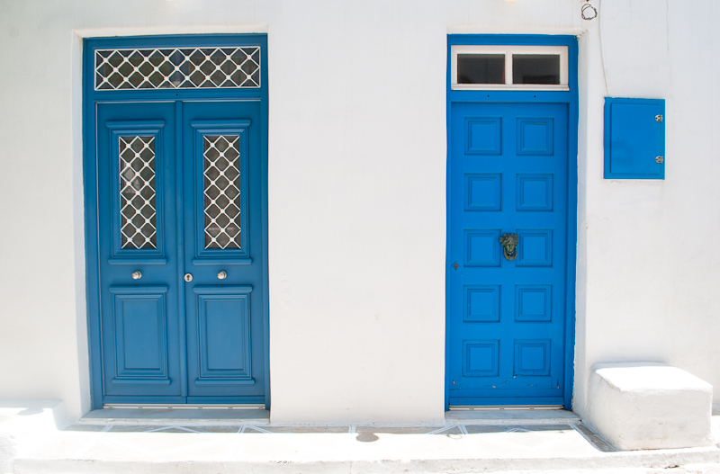 house with white walls and blue doors in greece mykonos