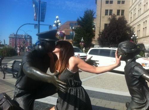 девушка целуется с памятником