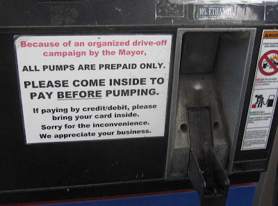 Gas pump with this sign attached: Because of an organized drive-off campaign by the Mayor, all pumps are prepaid only. Please come inside to pay BEFORE pumping.