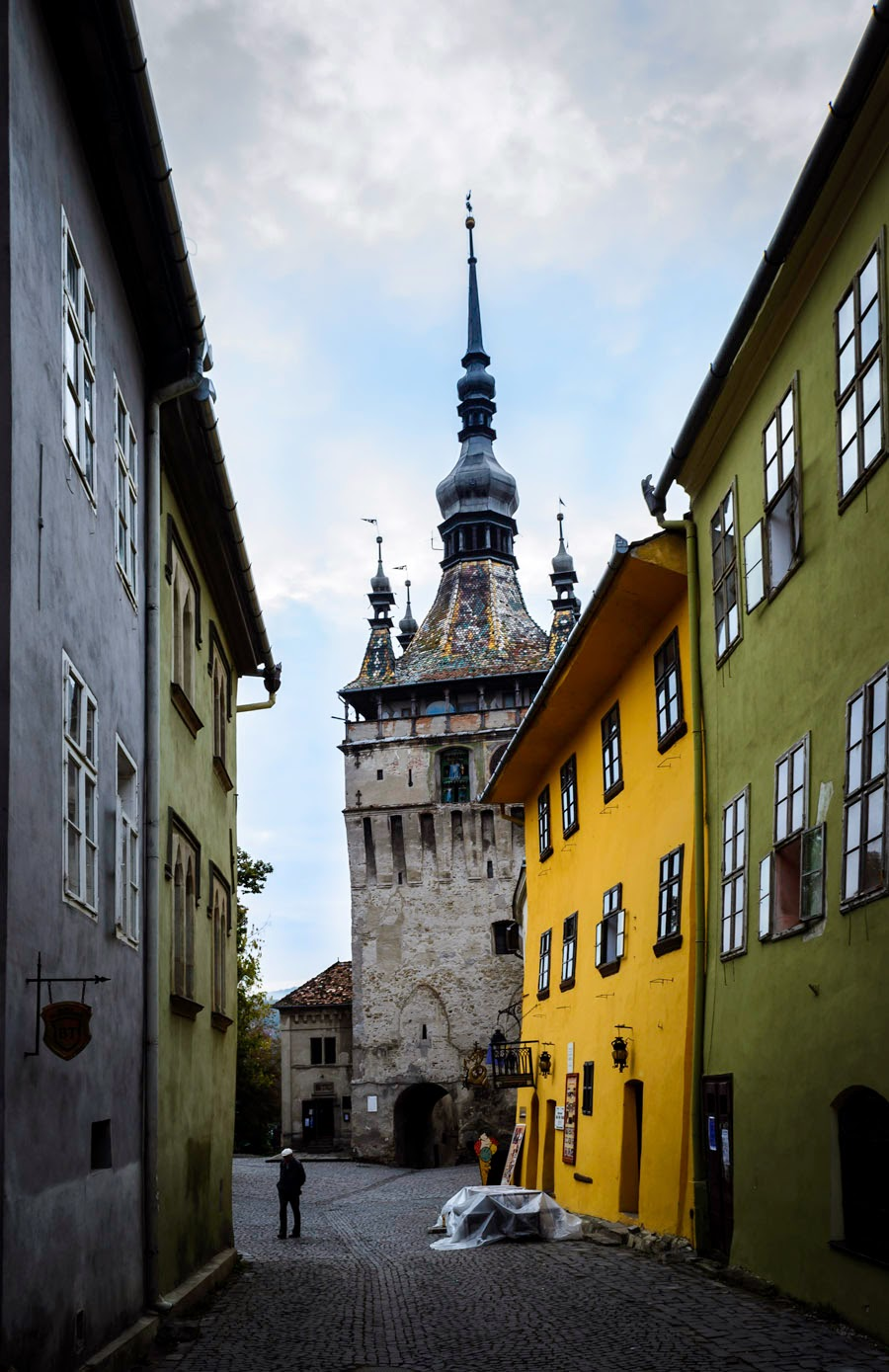 A narrow street in the Sighisoara medieval citadel and the Clock tower in the background on the photo
