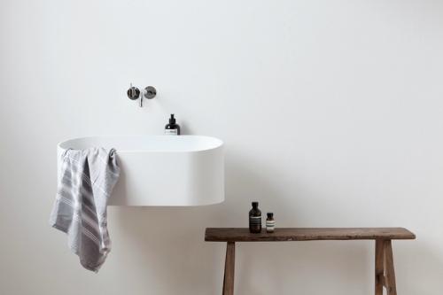 Ein minimalistischer Bad mit einem ungewöhnlichen Waschbecken aus glatten Cristalplant.