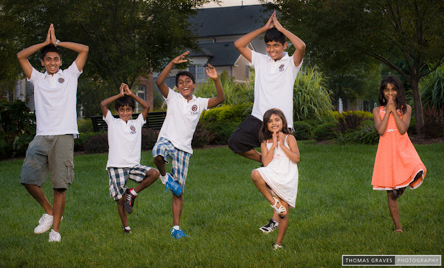 Several children attempt a yoga balancing pose in this photo.