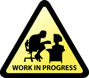This is a picture of a triangular sign with a person in front of a computer that says work in progress.