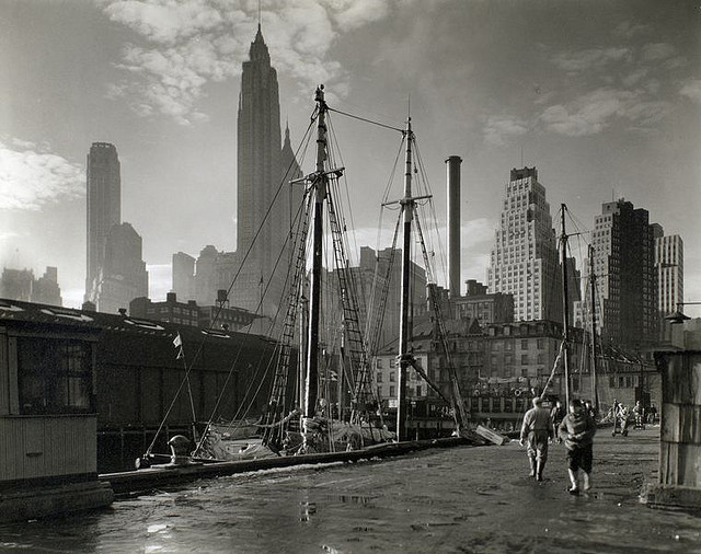Fulton Street Dock, Manhattan skyline, Manhattan. November 26, 1935. Notes: Code: I.D. Men walk on pier where sailing vessels are moored, skyline beyond. Source: Changing New York / Berenice Abbott. Repository: The New York Public Library. Photography Collection, Miriam and Ira D. Wallach Division of Art, Prints and Photographs.
