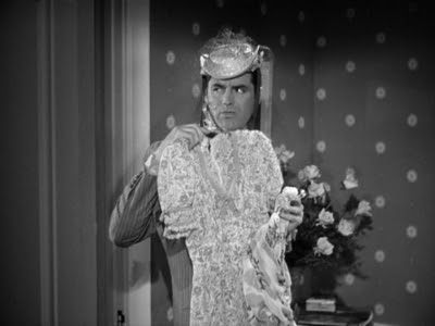 Cary Grant, wearing a hat, holding up a dress, looking in a mirror.