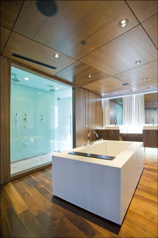 Picture of modern white bathtub and shower cabin built into the wall