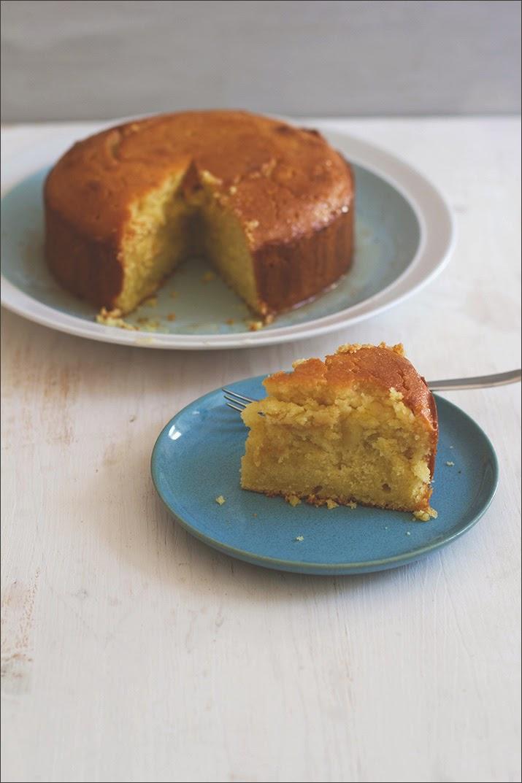 Ein Stück Semolina-Joghurt-Kuchen mit Zitronensirup auf dem Teller, im Hintergrund der angeschnittene Kuchen