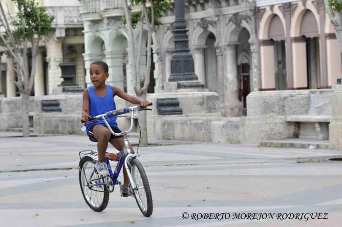 Niño montando bicicleta en el Paseo de Martí (Prado) en La Habana, Cuba, el 27 de junio de 2013