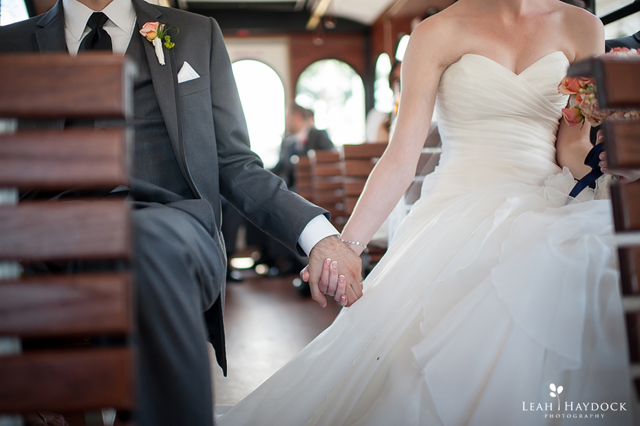 Bride and groom holding hands in wedding trolley