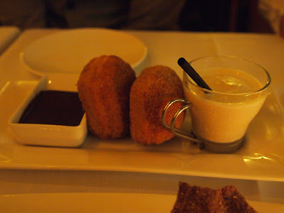 beignets served between venezuelan chocolate fondue and a shot class filled with vanilla-date milkshake