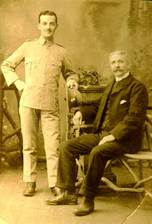 Studio portrait of two men, one standing in military uniform, the other, older sitting.