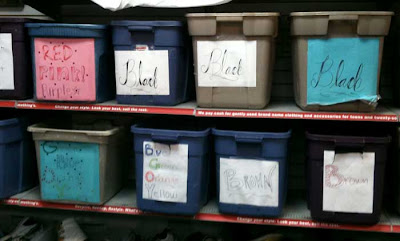 Gray bins on a shelf with hand-drawn cursive color names like Black, Red