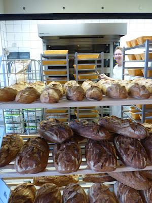 Blick durch viele Brote hindurch in Richtung Backofen