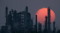 Sunset over refinery (Credit: AP Photo/Charlie Riede) Click to Enlarge.