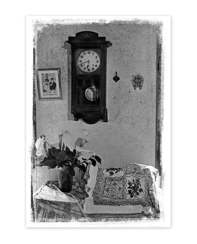 Relógio de pêndulo na parede e em baixo, numa mesa coberta com uma toalha, uma jarra com jarros brancos e uma almofada bordada