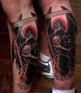 Death tattoo on the leg: Grim Reaper holding a skull