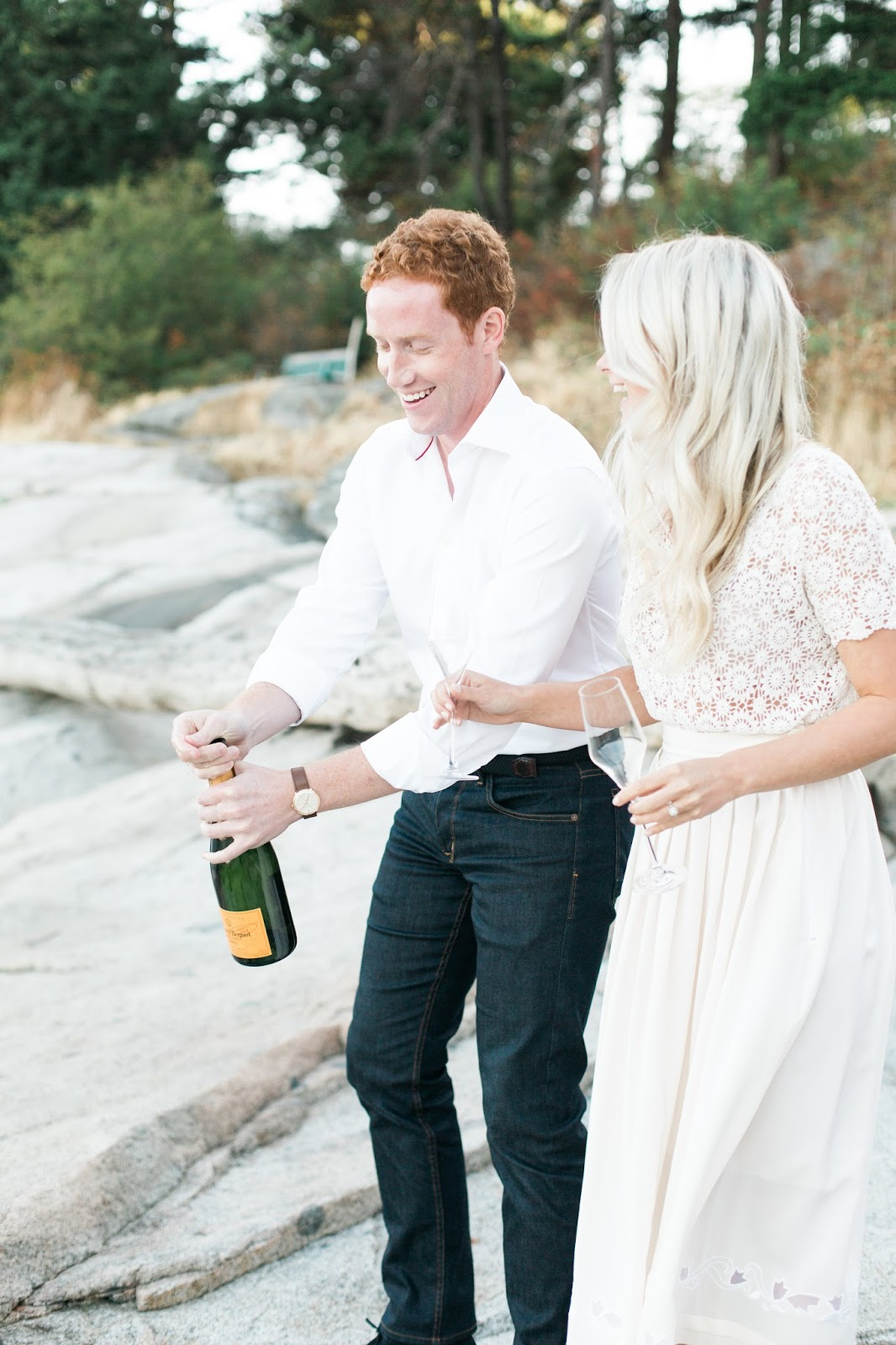 popping champagne at an engagement photo shoot
