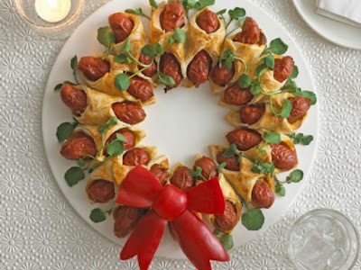 hotdogs wrapped in pastry placed in a ring and baked. Decorated with edible red bow.