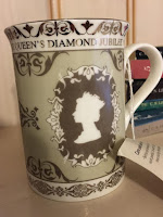 An English tea mug with a portrait of Queen Elizabeth the second in cameo on the side.
