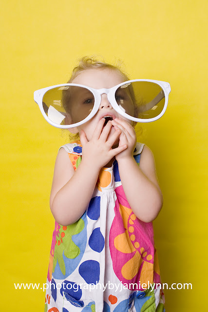 little girl studio yellow backdrop big sunglasses