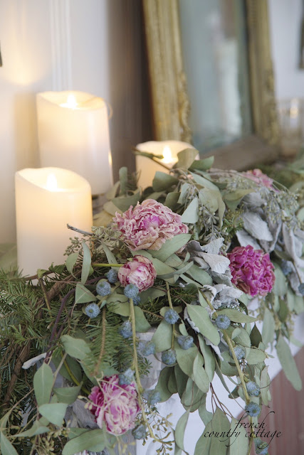 Close up of candles and dried garland on mantel