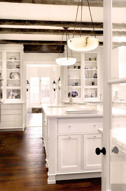 Kitchen with exposed beams, alabaster pendant lights hanging above the kitchen island, white cabinets and a wood floor