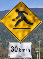 road sign - person running after a ball