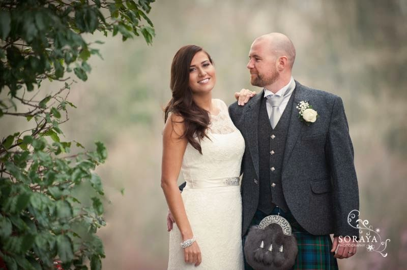 bride and groom photographed in the gardens of ardoe house. the bride is wearing a lace bridal gown with soft wavy hairstyle
