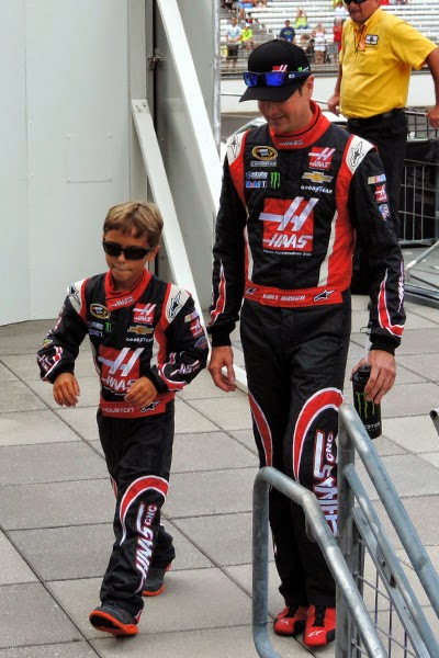 "This photo is the winner of ""cutest"" - Kurt Busch walked through driver introductions with nine-year-old Houston Hermanstorfer, Kurt's girlfriend, Patricia Driscoll's son.  #crownheroes #jww400 #reignon #nascar"