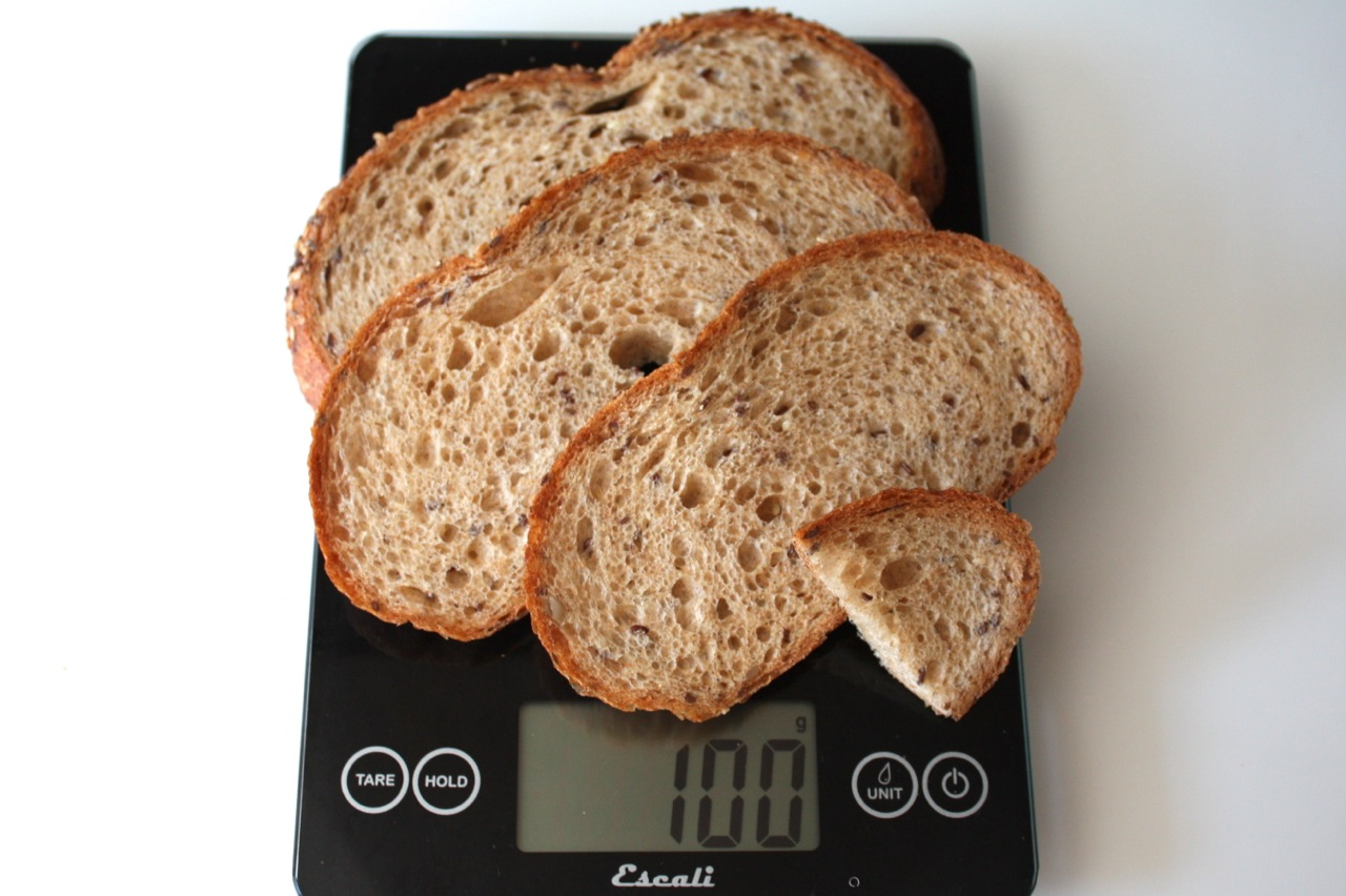 100 grams of seven grain bread shown on digital scale