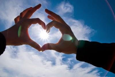 Dos manos formando un corazón contra el cielo con el sol en la mitad