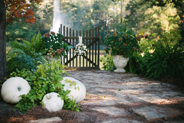 wedding day alter with stone pavers and white pumpkins and wooden gate