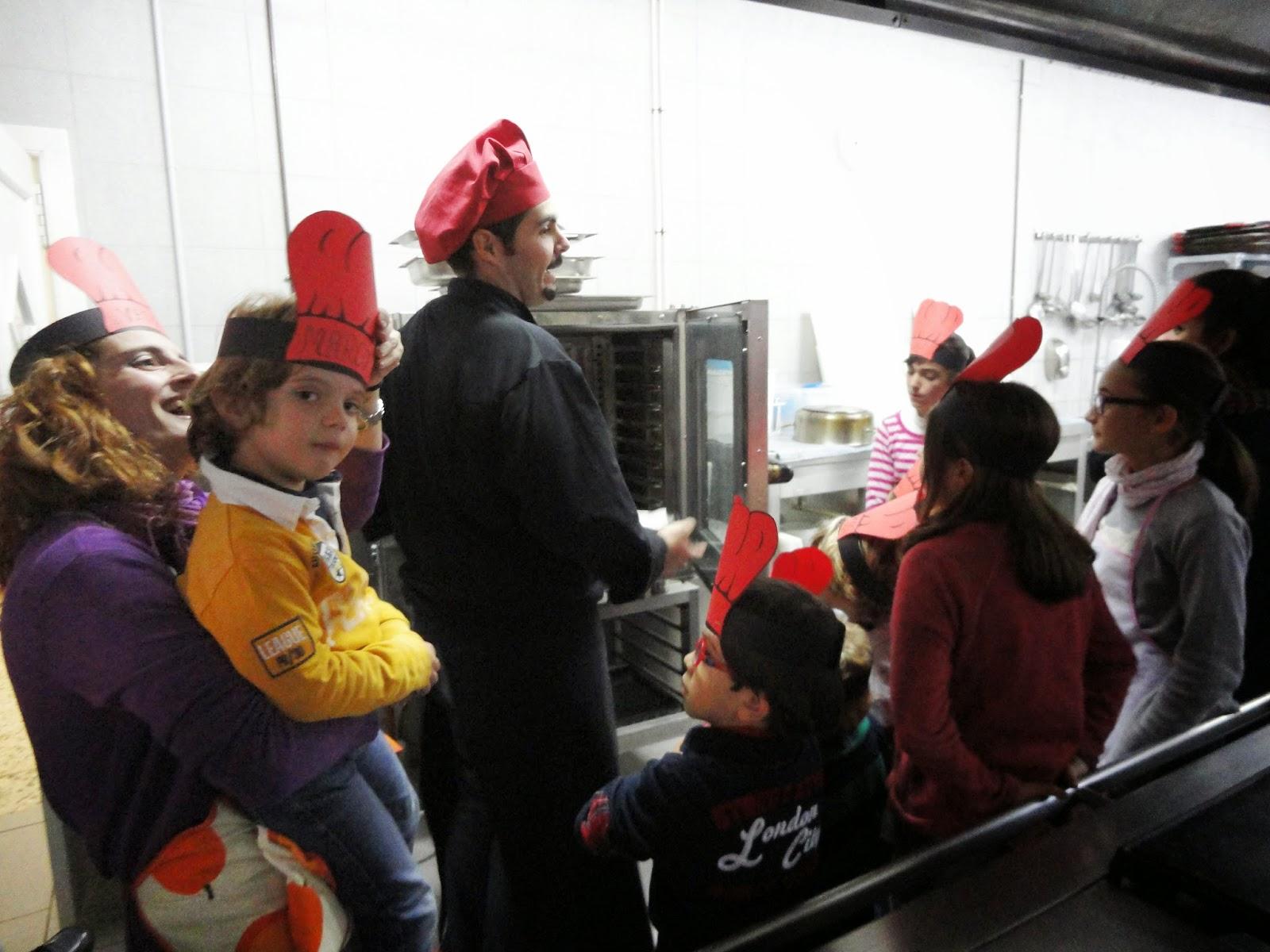 el chef y todos los niños esperan junto al horno a que se hagan las magadalenas y galletas