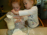 Children sifting flour into a bowl.