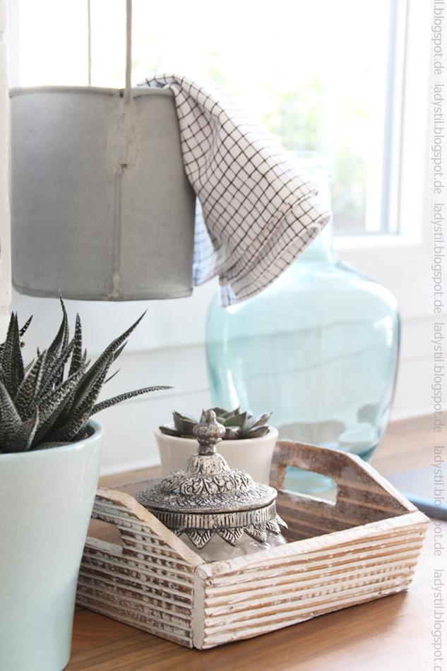 kleine Glasdose mit silbernem Deckel auf einem kleinen Holztablett neben einem türkisen Übertropf mit Sukkulente im Hintergrund eine hellblaue bauchige Glasflasche