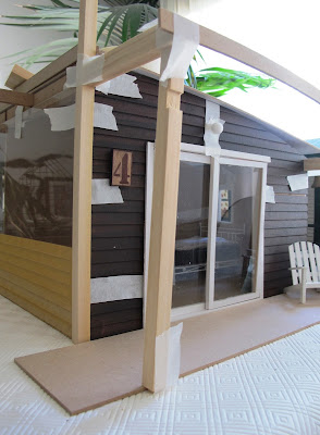 Dry fit of a dolls' house shed kit, with stained weatherboarding taped to the sides and pergola posts and struts taped in place.