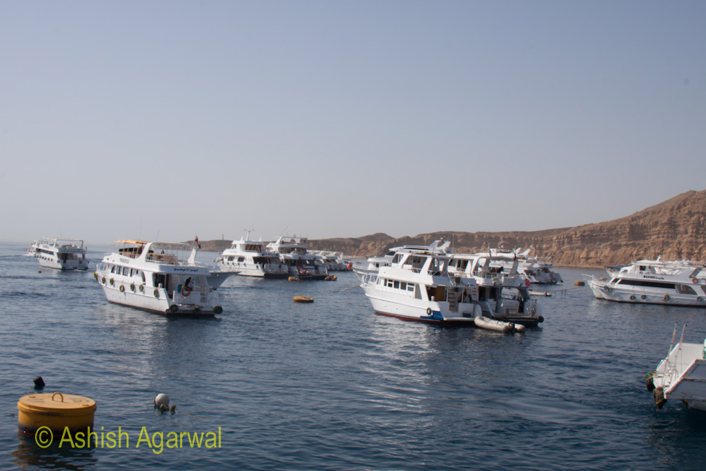 Small ships and boats in the harbour of Sharm el Sheikh in the Red Sea in Egypt with backdrop of hills