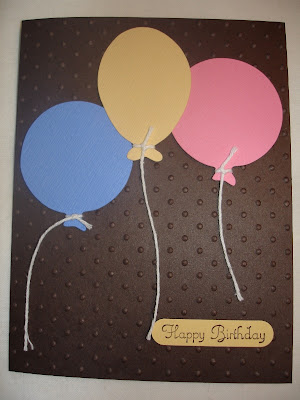 Brown card embossed with polka dots and three die-cut balloons (pink, yellow and blue).
