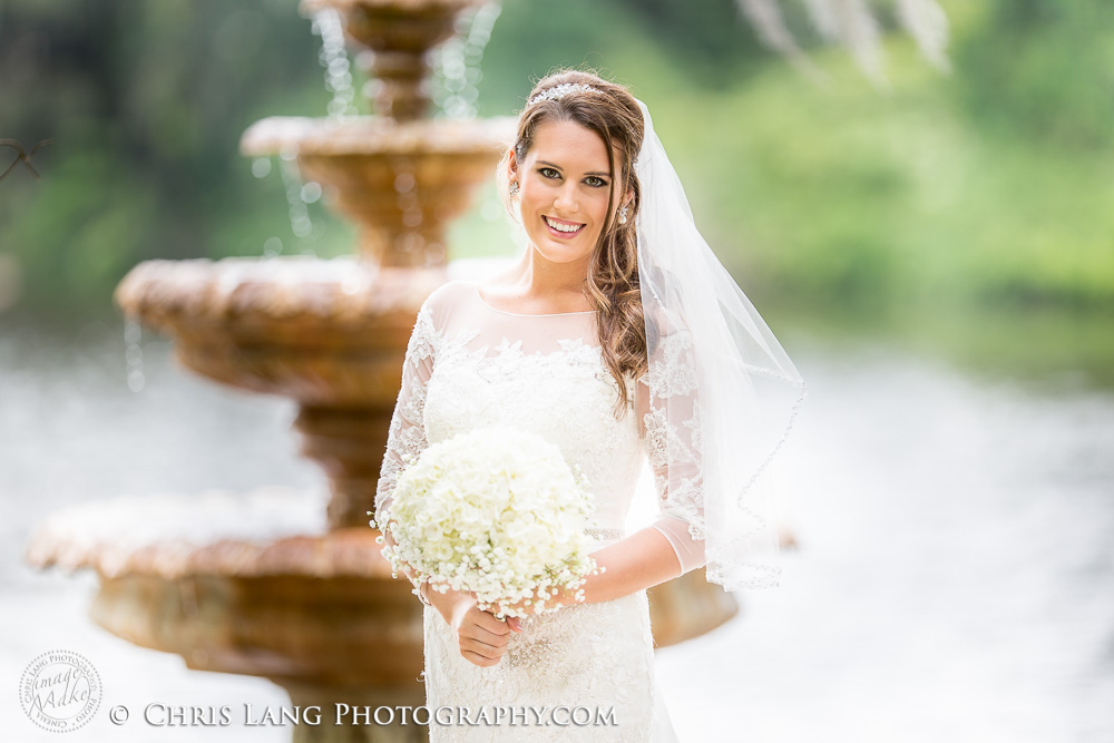 Image of bride at Airlie Gardens at the fountain in her wedding dress