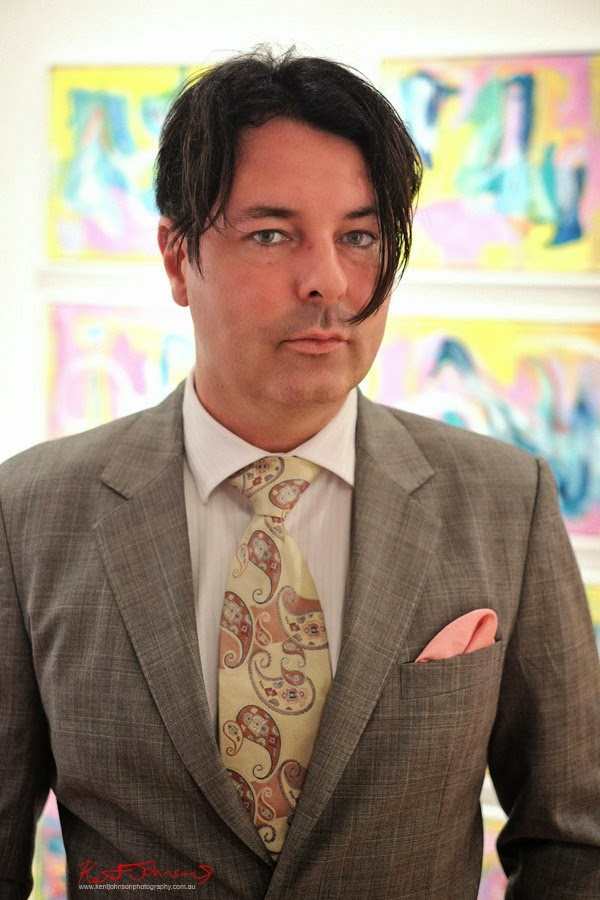 Artist portrait, Trenton Shipley in paisley tie and grey suit, pink pocket handkerchief at Gallery Eight - Photo by Kent Johnson.